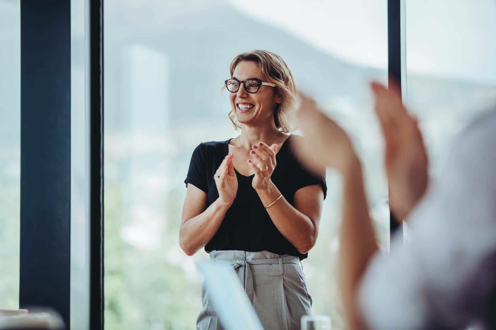 Businesswoman clapping hands after successful brainstorming session in boardroom. Business people women applauding after productive meeting.